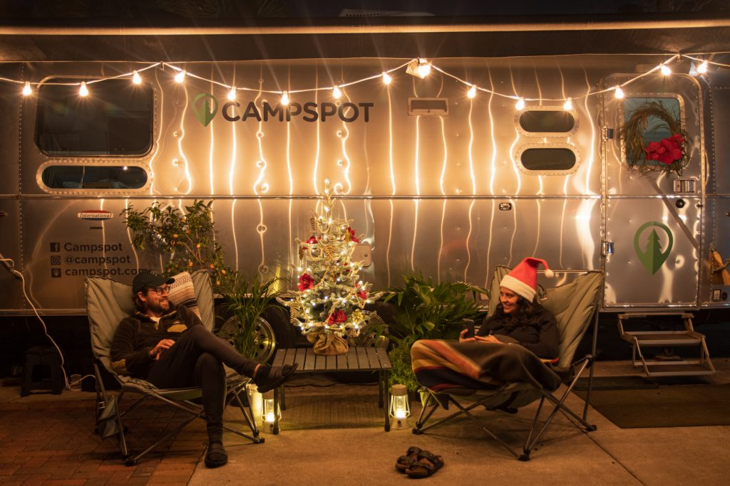A man and a woman sit outside on camping chairs with a lit miniature Christmas tree between them. They are under an awning of an Airstream trailer.