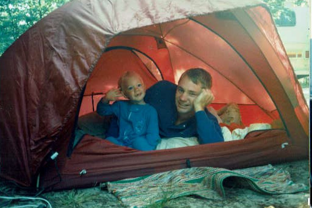 A man and baby in a red tent.