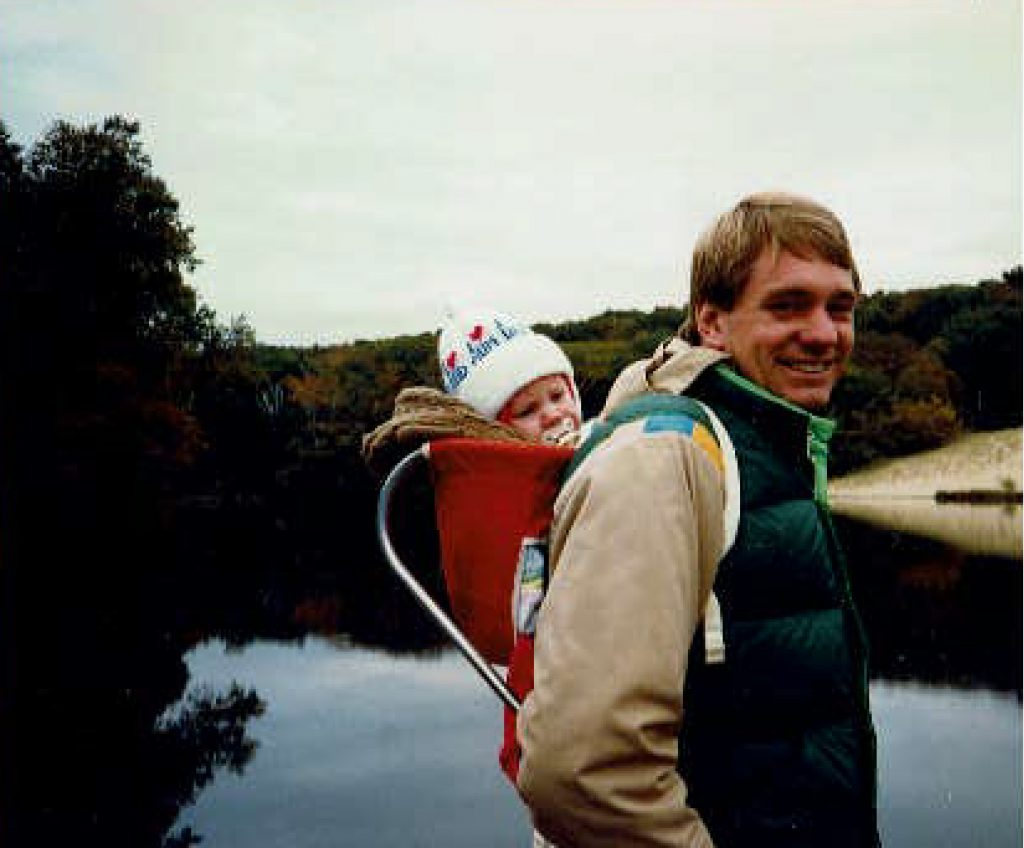 A man hiking with a baby on his back with water in the background.