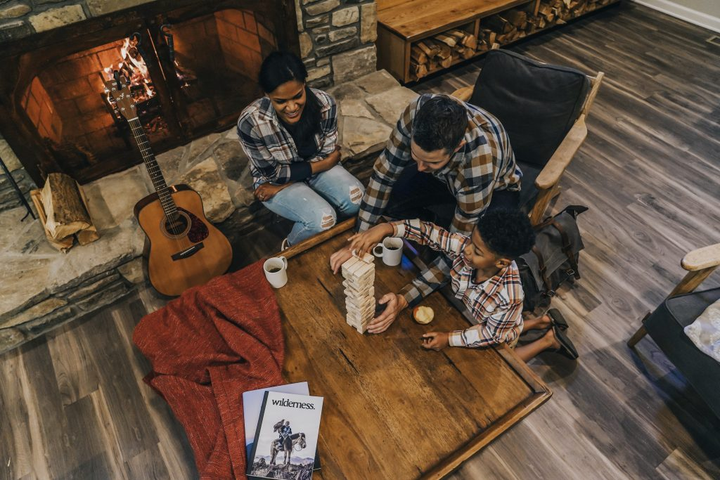 Family playing jenga around the fireplace while camping in cabin.