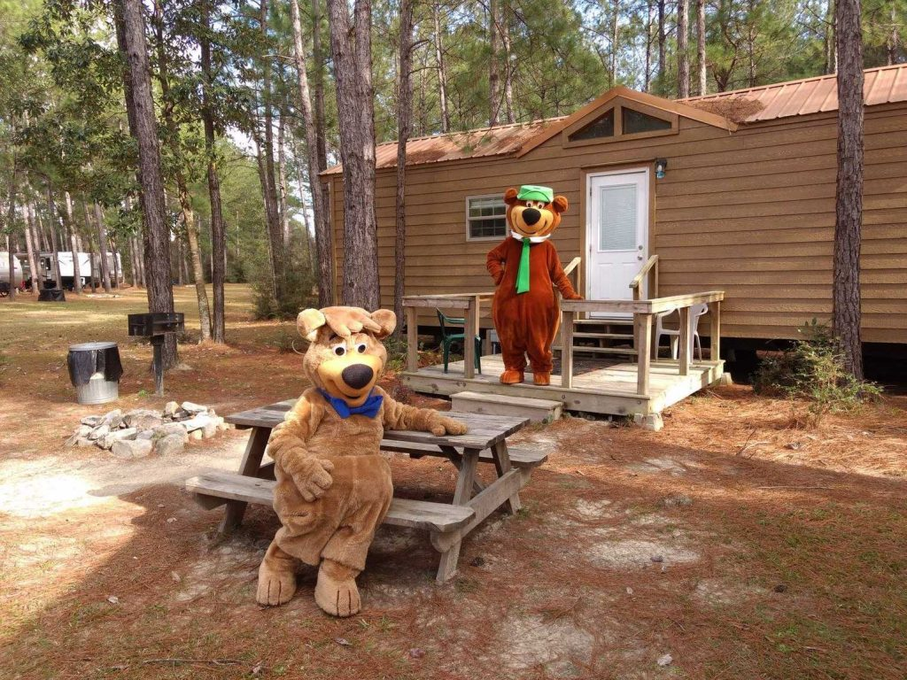 Yogi bear standing in front of a cottage at Yogi Bear's Jellystone Park™ Camp-Resort: Alabama Gulf Coast in Elberta, AL