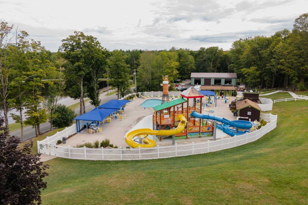 Fenced in pool are with waterslides surrounded by forest at Yogi Bear's Jellystone Park™ Camp-Resort: Birchwood Acres in Greenfield Park, NY