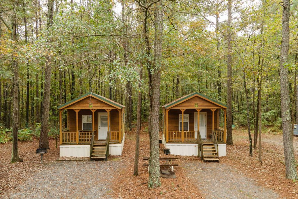 Two cabins in the woods with picnic table in between at Yogi Bear's Jellystone Park™ Camp-Resort: Emporia in Emporia, VA
