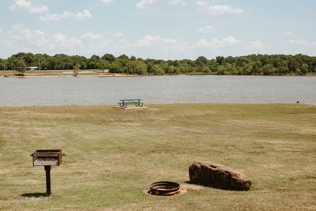 Campground on the water with picnic table and fire pit at Yogi Bear's Jellystone Park™ Camp-Resort: Eufaula in Eufaula, OK