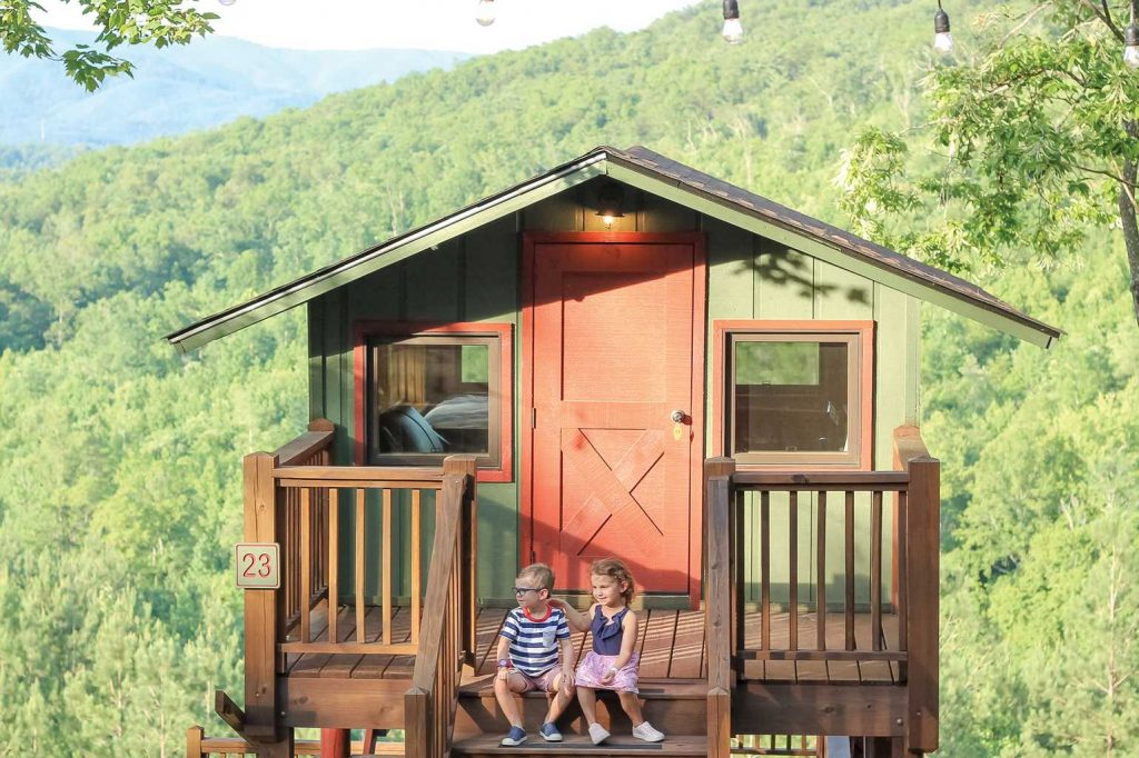 Two kids in a tree top cabin with forest in the background at Yogi Bear's Jellystone Park™ Camp-Resort: Golden Valley in Bostic, NC