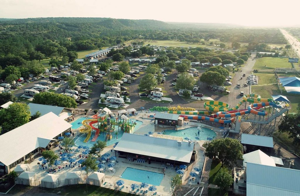 Image taken from above of pool, waterpark, waterslides, RVs, and mountains at Yogi Bear's Jellystone Park™ Camp-Resort: Guadalupe River in Kerrville, TX