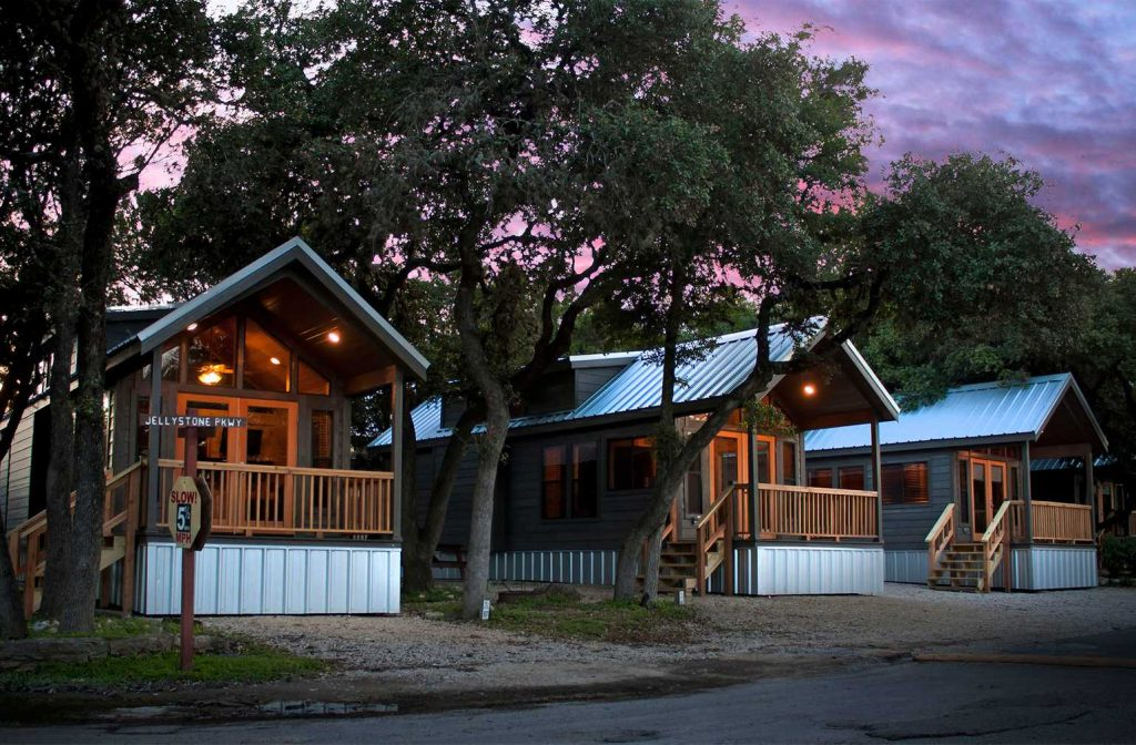Cabins surrounded by trees during sunset at Yogi Bear's Jellystone Park™ Camp-Resort: Hill Country in Canyon Lake, TX