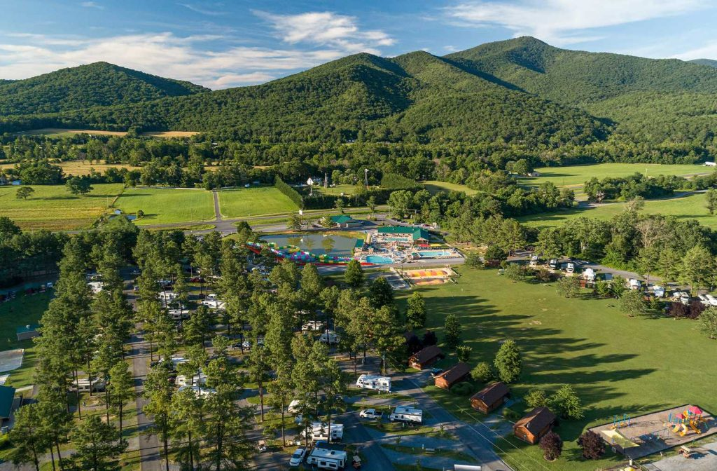 Image taken from above of campground with RVs, pool, and mountains in the background at Yogi Bear's Jellystone Park™ Camp-Resort: Luray in Luray, VA