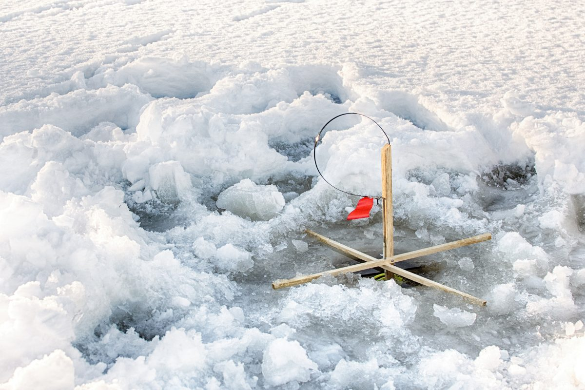 Ice fishing trap waits patiently for fish under the ice on a lake in Maine. Wildfox Cabins & Campground in Lakeville, Maine, is the perfect winter camping getaway in the northeast coast.