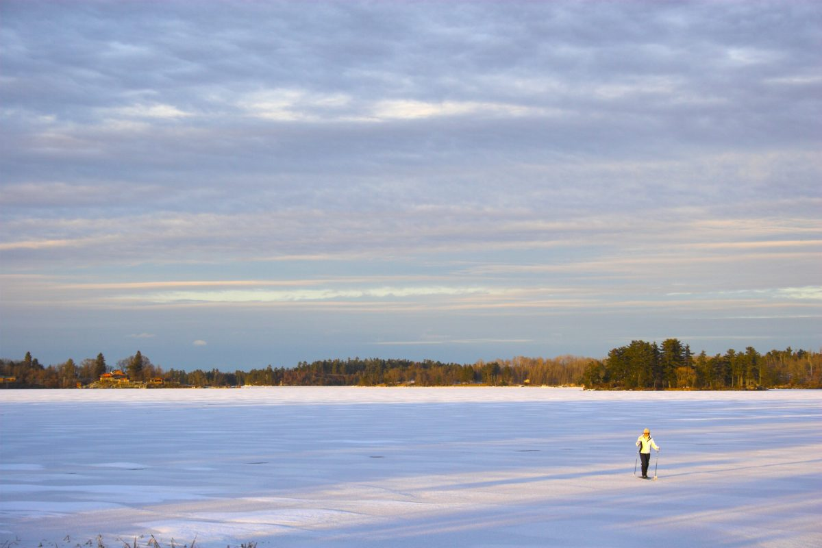 A woman cross-country skis across a frozen lake in northern Minnesota. The Canary Beach Resort gives those from Minneapolis the perfect winter camping getaway.