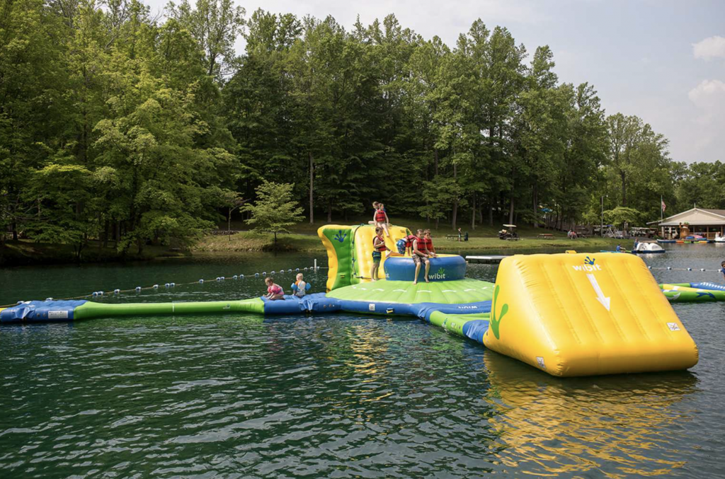 Inflatable challenge course on the lake with kids playing at Yogi Bear's Jellystone Park™ Camp-Resort: Mt. Gilead in Mt. Gilead, OH