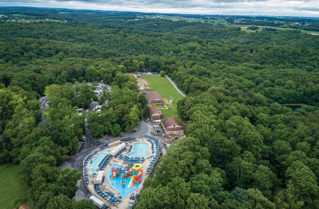 Image taken from above of pool, waterslides, and RVs surrounded by forest at Yogi Bear's Jellystone Park™ Camp-Resort: Quarryville in Quarryville, PA