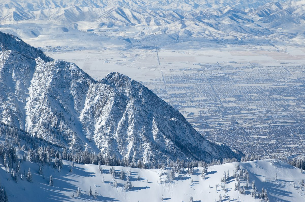An aerial view of Salt Lake City in the winter and covered with snow. The view is from a nearby ski resort. This area's winter camping getaway is the Pony Express RV Resort & Campground in North Salt Lake, Utah.