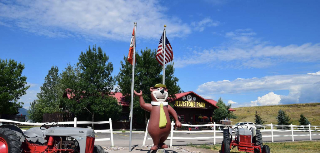 Yogi bear waving in front of entrance at Yogi Bear's Jellystone Park™ Camp-Resort: Missoula in Missoula, MT