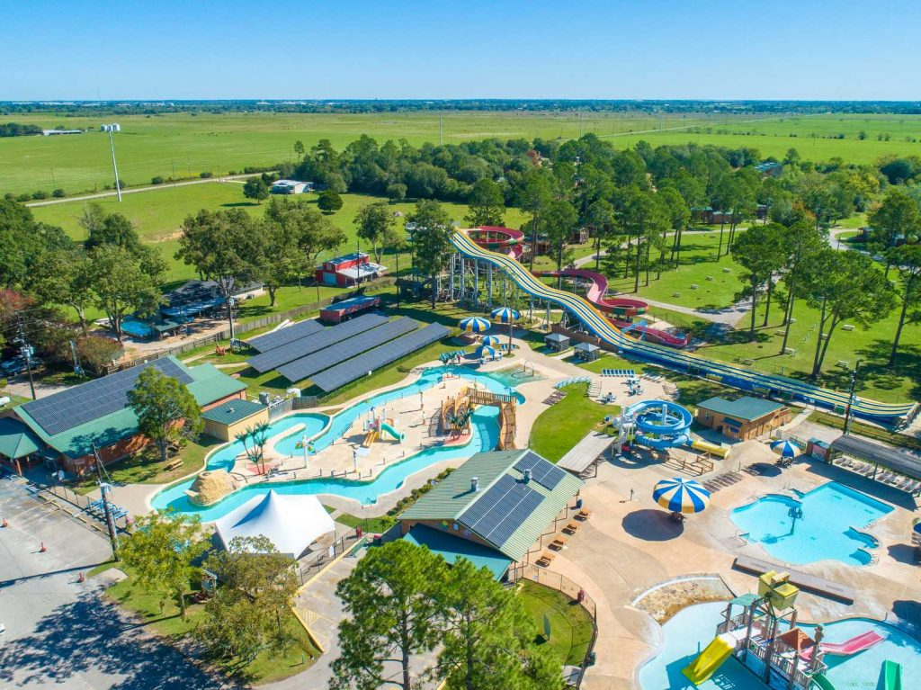 Picture taken from above of pool, lay river and waterslides with trees in the background at Yogi Bear's Jellystone Park™ Camp-Resort: Waller in Waller, TX