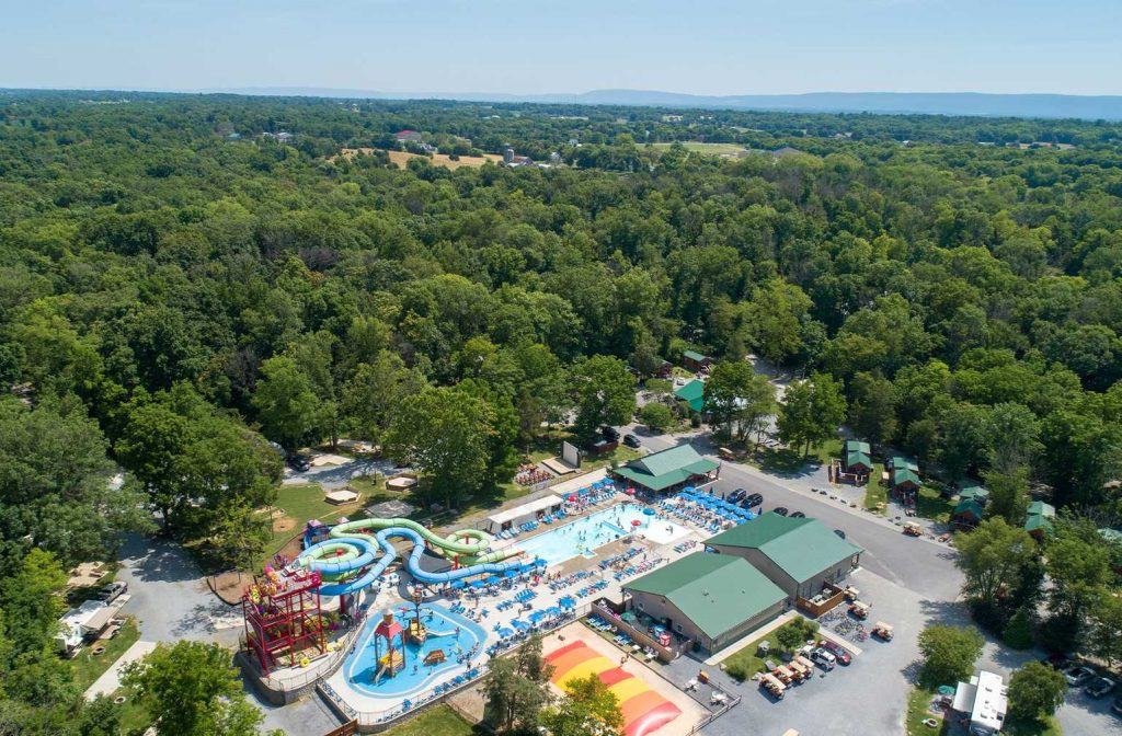Drone shot from above of waterpark, cabins, and forest at Yogi Bear's Jellystone Park™ Camp-Resort: Williamsport in Williamsport, MD