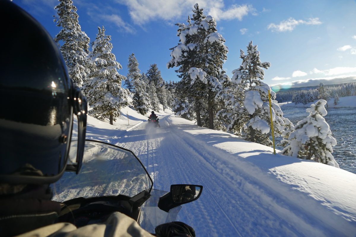 A person snowmobiles down a pass in Yellowstone National Park in Wyoming. Snow covers the trees on both sides of the pass. Wapiti Lodge is Yellowstone's winter camping getaway.