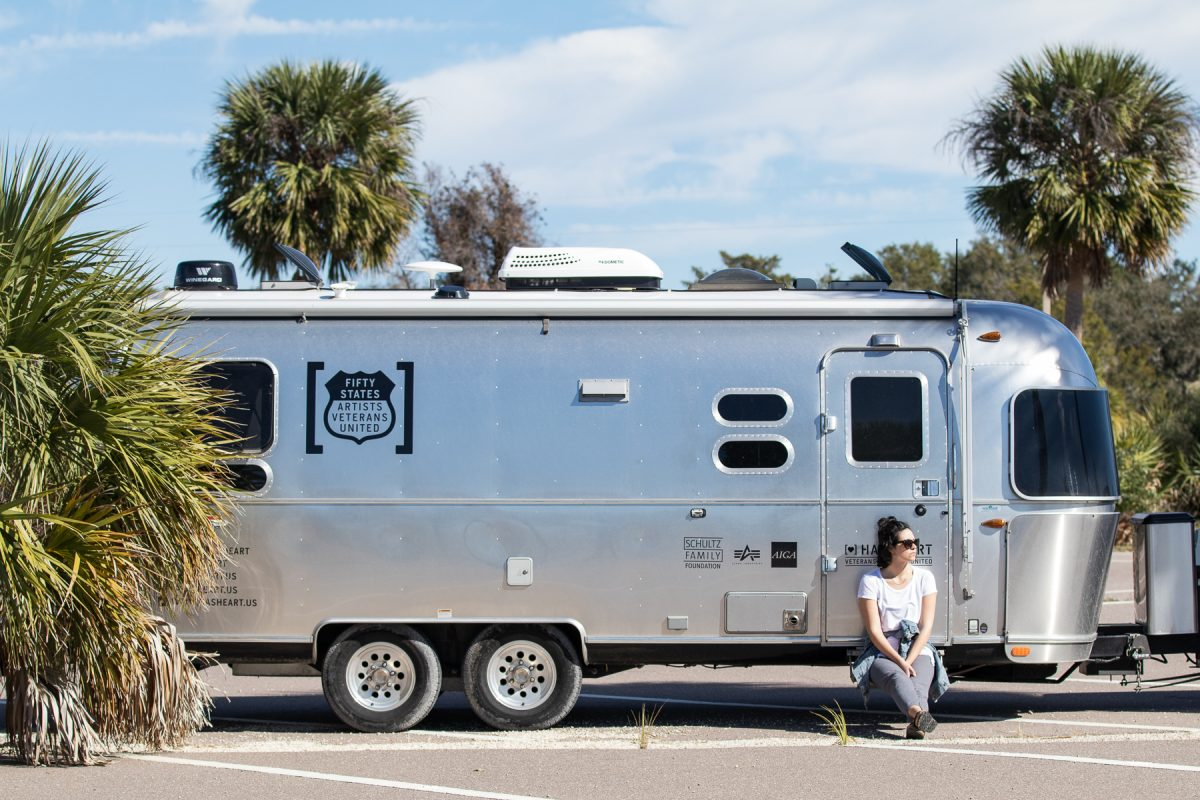 A woman sits on the steps of an Airstream trailer parked at a Wal-Mart parking lot. Wallydocking is staying in a Wal-Mart parking lot overnight.