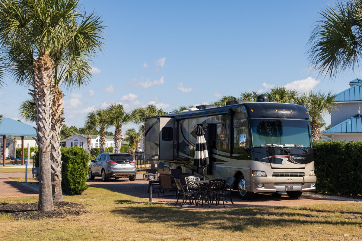 A Class A motorhome coach sits at a campsite at Emerald Coast RV Resort in Panama City Beach, Florida. The RV is surrounded by palm trees.