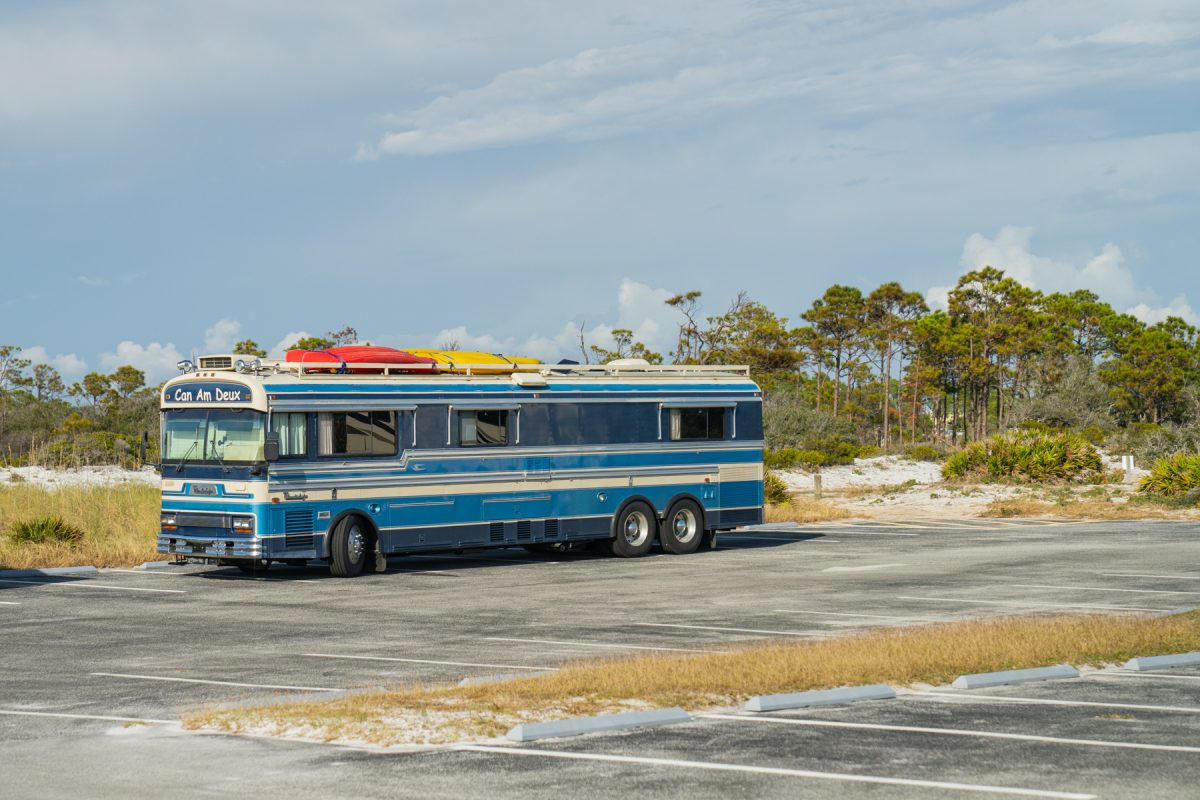 A blue motorhome RV with canoes tied to the top sits in a parking lot surrounded by dunes.