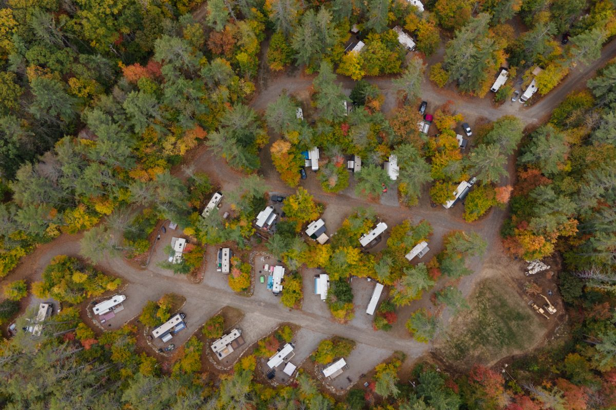 An aerial view of Ames Brook Campground in Ashland, New Hampshire with RV's spaced out and sitting in their campsites. The fall foliage can be viewed with bright colors poking out.