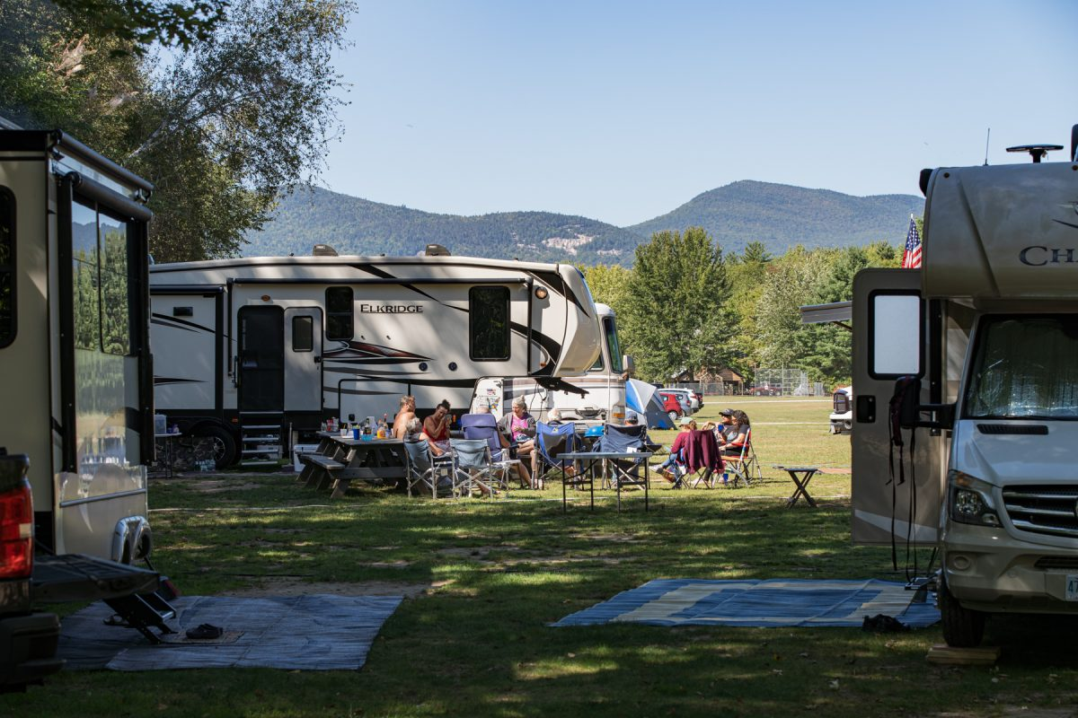A fiver fifth-wheel trailer sits in a valley surrounded by mountains and other RVs and campers congregate together sitting in campchairs.