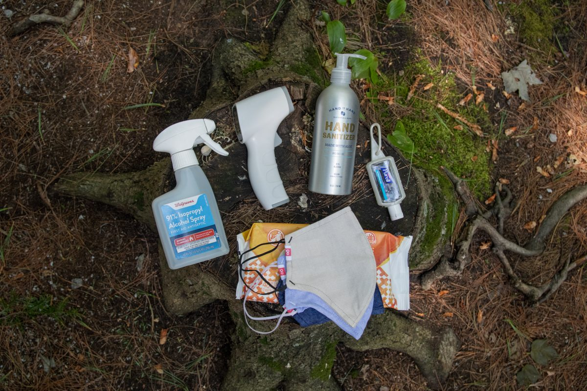 A variety of PPE including rubbing alcohol, a thermometer, hand sanitizer, and face masks laid out on the ground.