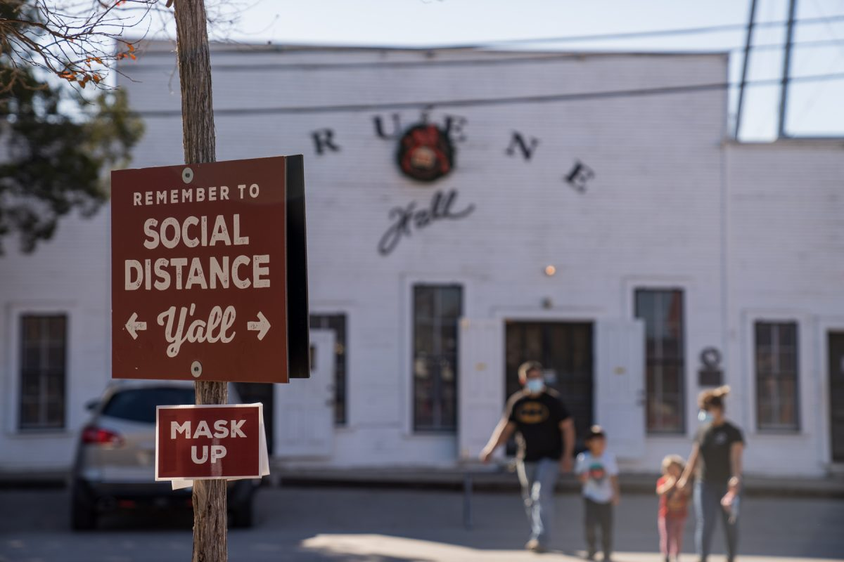 A sign reminding visitors to social distance and wear a mask to prevent the spread of the coronavirus COVID-19 virus in Gruene, Texas.
