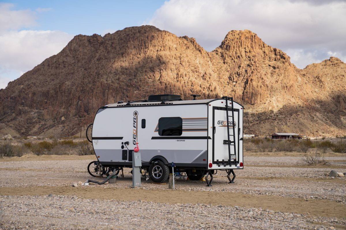 An RV sits on a campsite at Road Runners Travelers Campground in Terlingua, Texas with Bee Mountain in the background. The RV has stabilizing jacks to prevent rocking motion when people are in the RV.