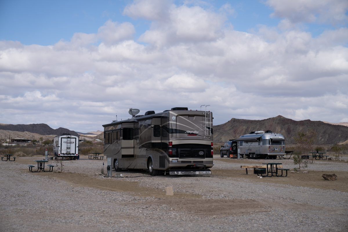 A Class A motorhome coach sits at a campsite at Road Runner Travelers Campground in Terlingua, Texas. A hula skirt is attached to the back of the RV to prevent rocks from flying up behind the motorhome.