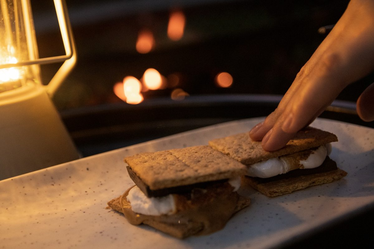 Someone finishes making a s'more by pressing a graham cracker down on the melted marshmallow.