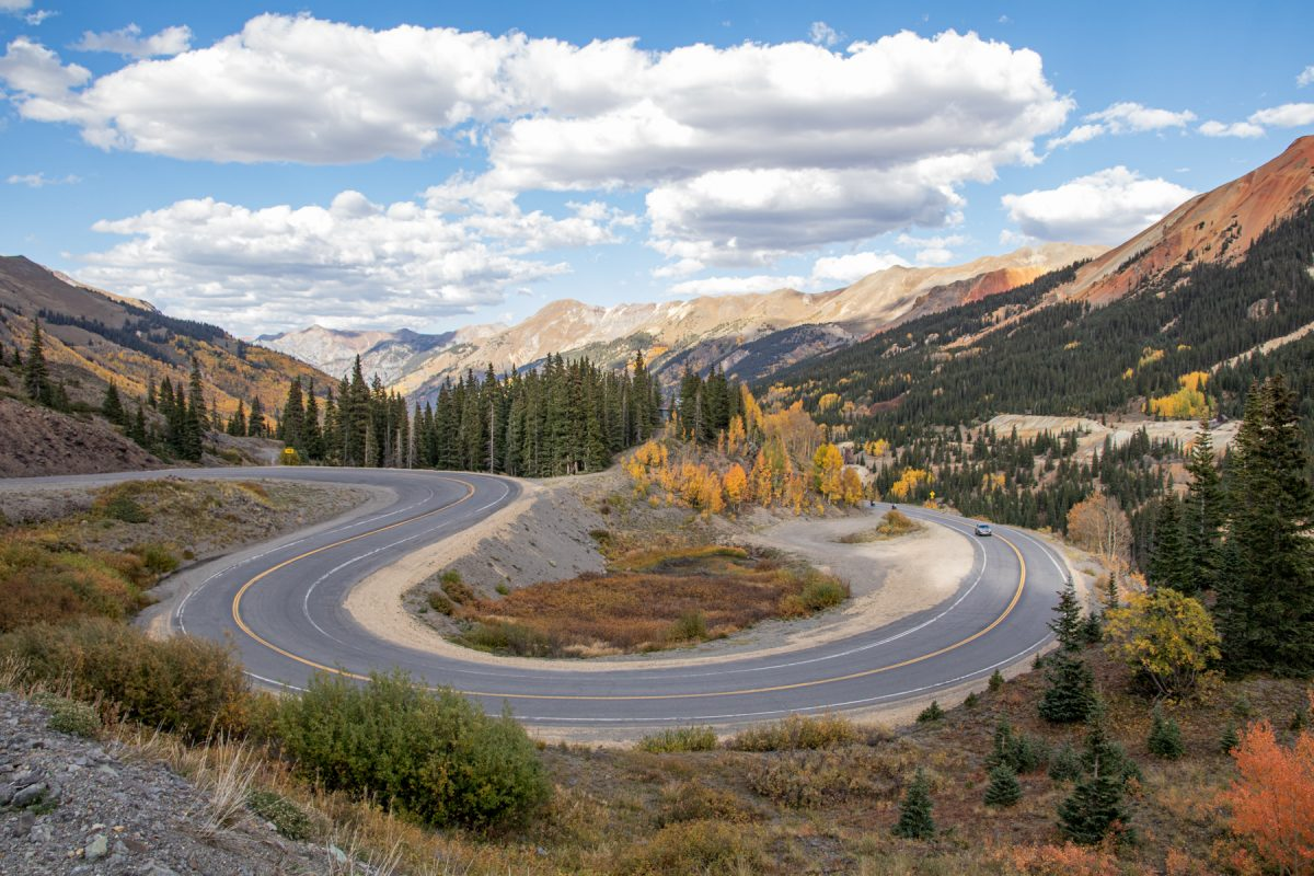 A car veers around the bend on the Million dollar highway in Colorado. In the background are the Rocky mountains.