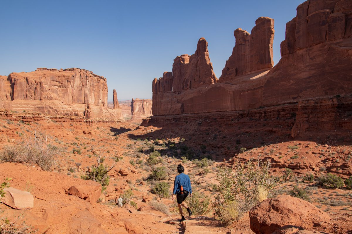 A woman hikes along the Park Avenue Trail in Arches National Park in Moab, Utah. The Courthouse Towers can be seen at the end of the trail.