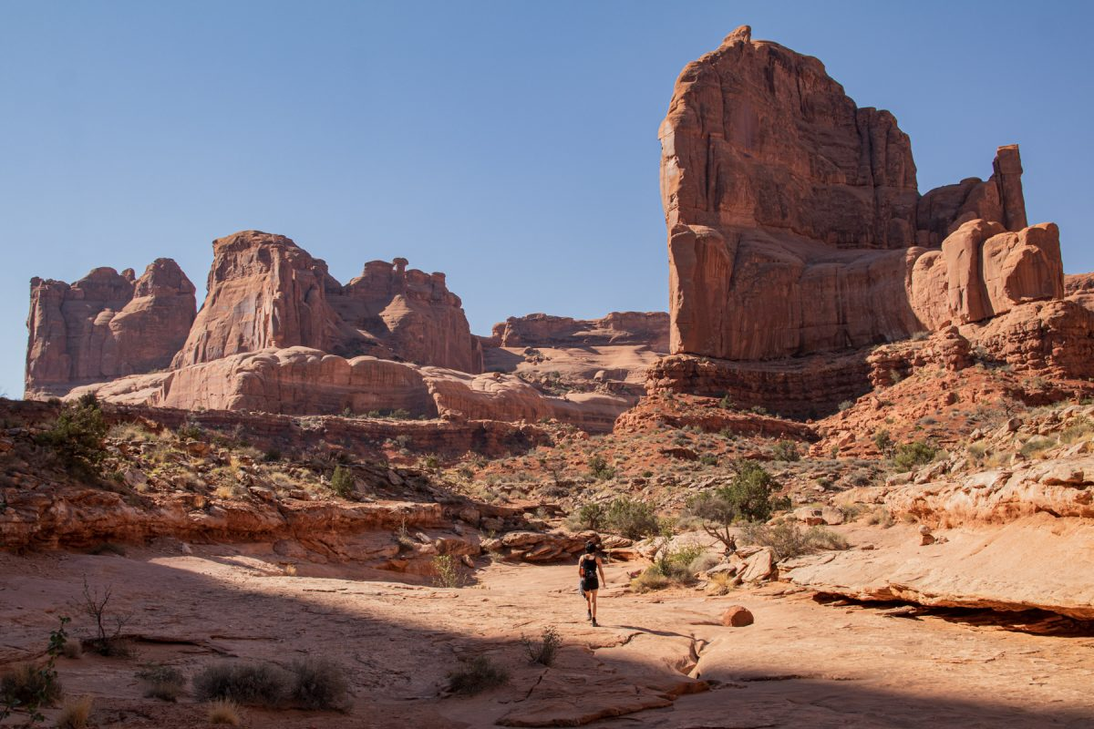 A woman hikes the Park Avenue & Courthouse Tower trail in Arches National Park in Moab, Utah.