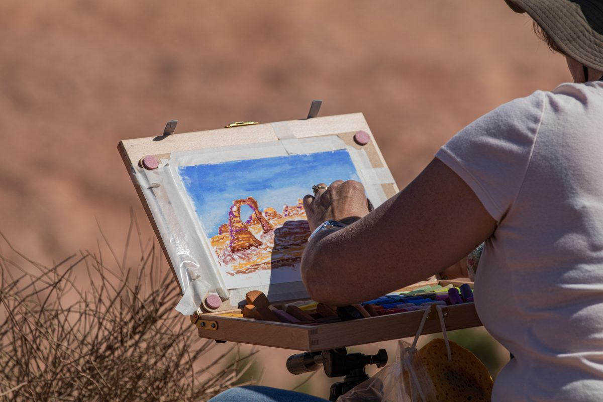 A woman uses pastels to depict the famous Delicate Arch in Arches National Park in Moab, Utah.