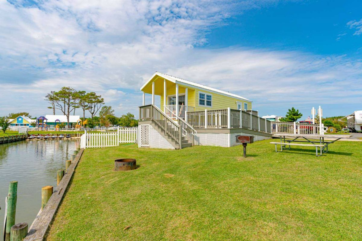 Yellow glamping cabin on the water at Castaway RV Resort.