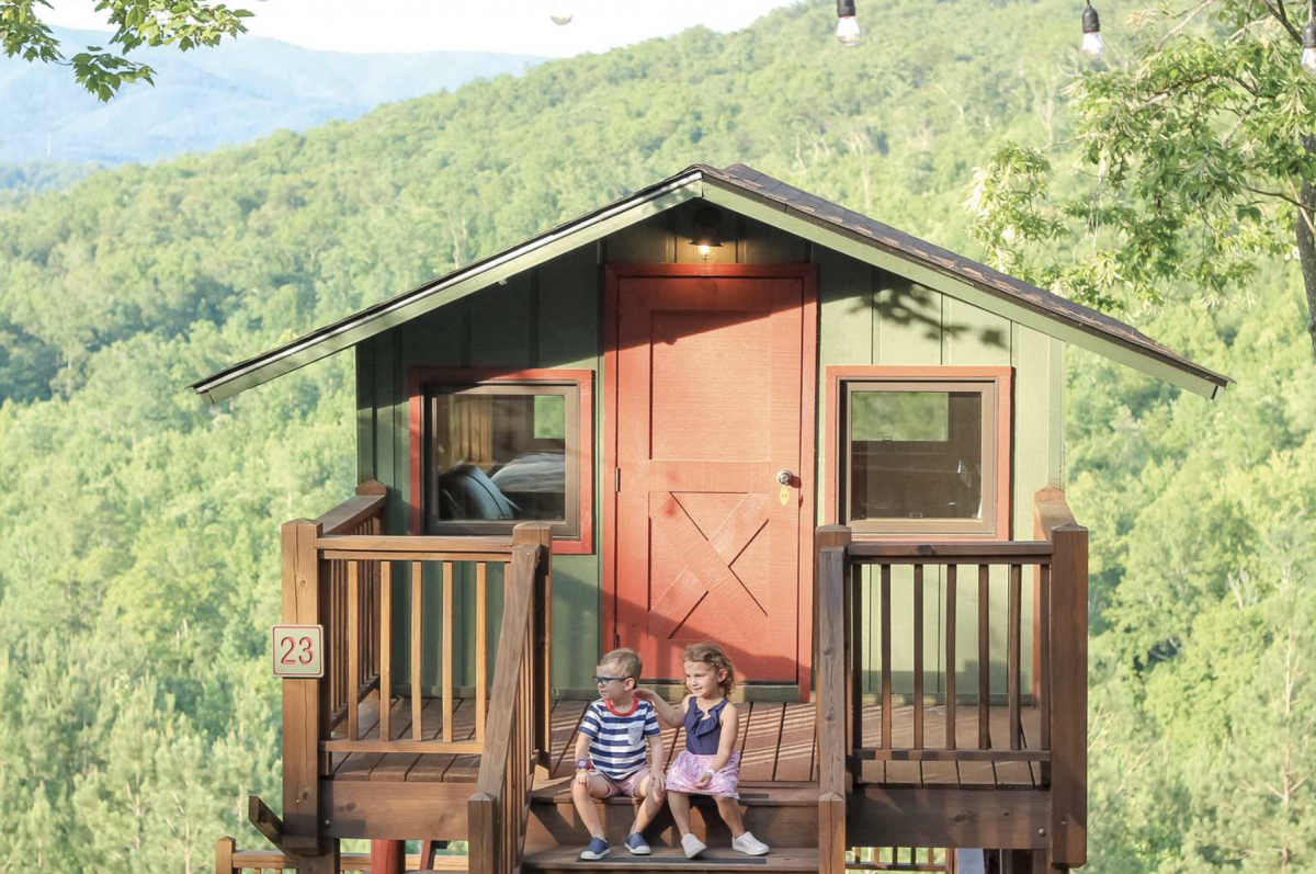 Two children sitting in a tree top cabin with trees in the background at Golden Valley.