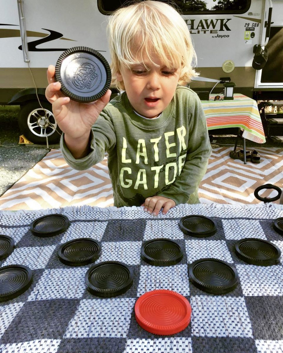 Boy playing checkers at campground in front of RV.