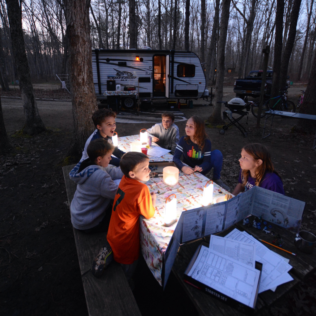 Kids around picnic table at campground playing a game.