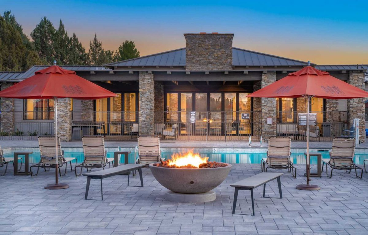 Outdoor pool area at sunset with fireplace at Verde Ranch RV.