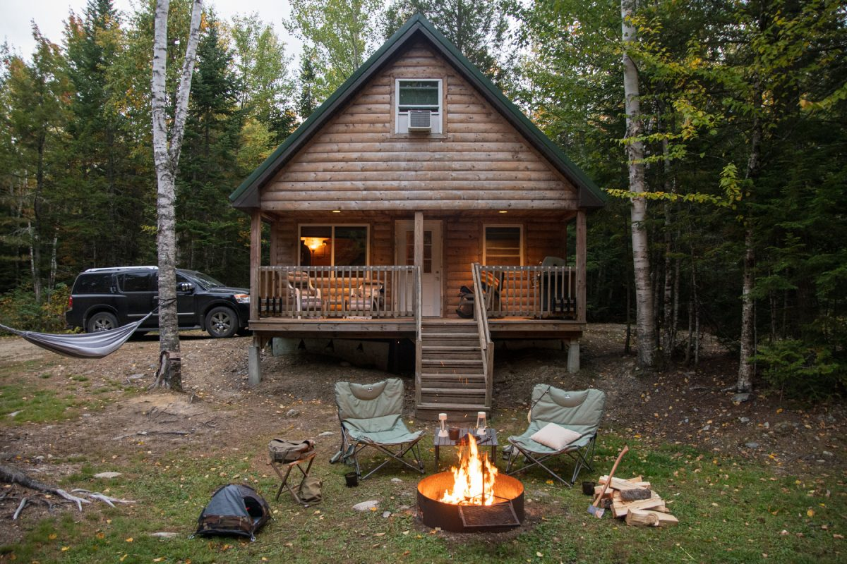 Cozy cabin with a fireplace and two camping chairs at Wild Fox Cabins & Campground.