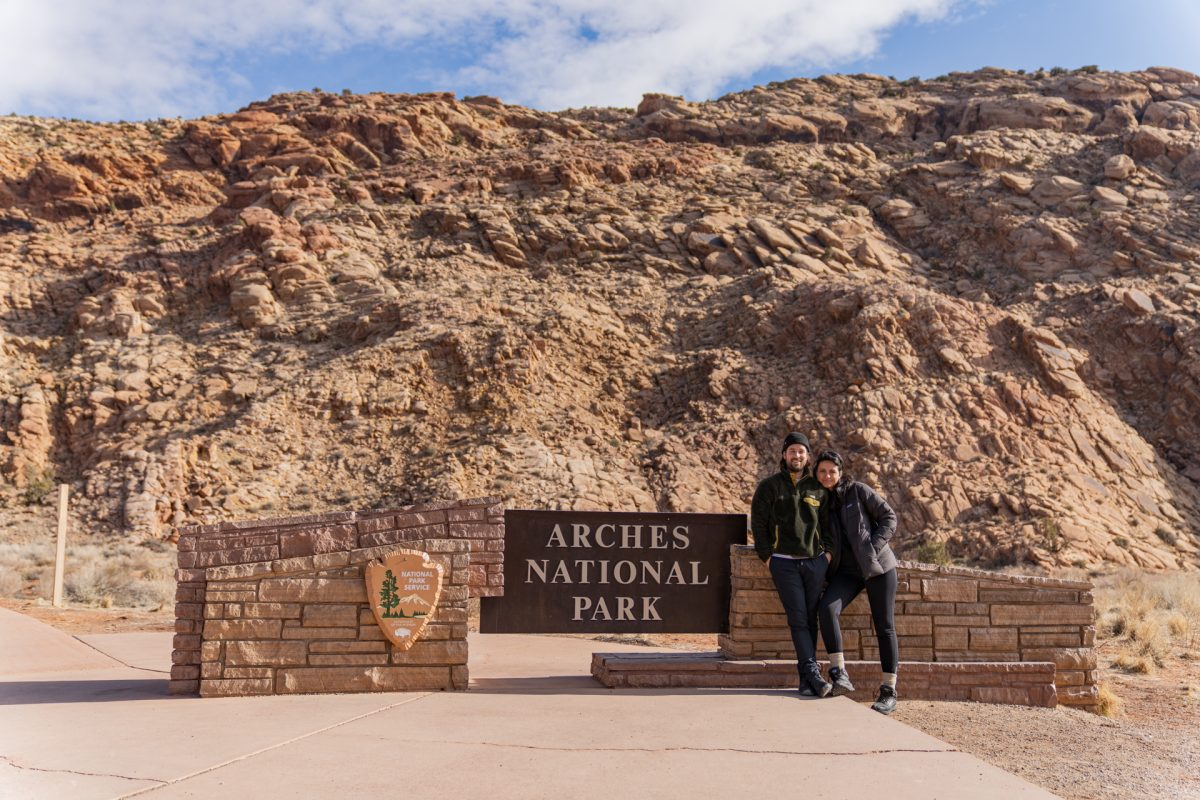 A man and a woman pose in front of the Arches National Park sign in Moab, Utah. Utah's famous red rock can be seen in the background.