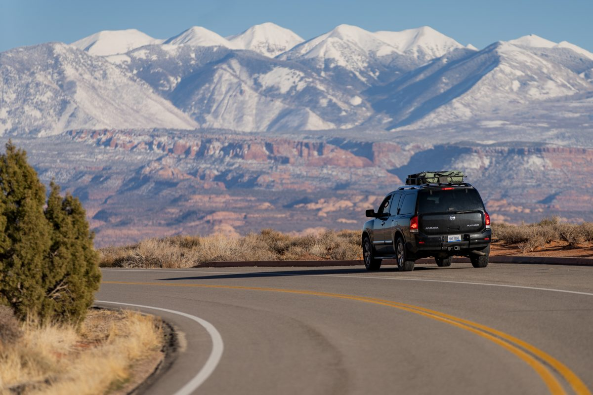 A black SUV is parked on a pull out that looks toward the La Sal Mountains. The mountains are covered in white snow.