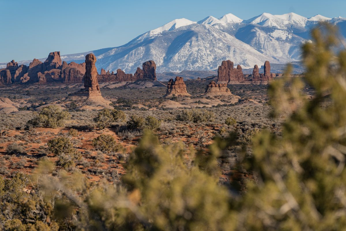 The La Sal Mountain range sits in front of the red rock formations of Arches National Park in Moab, Utah.