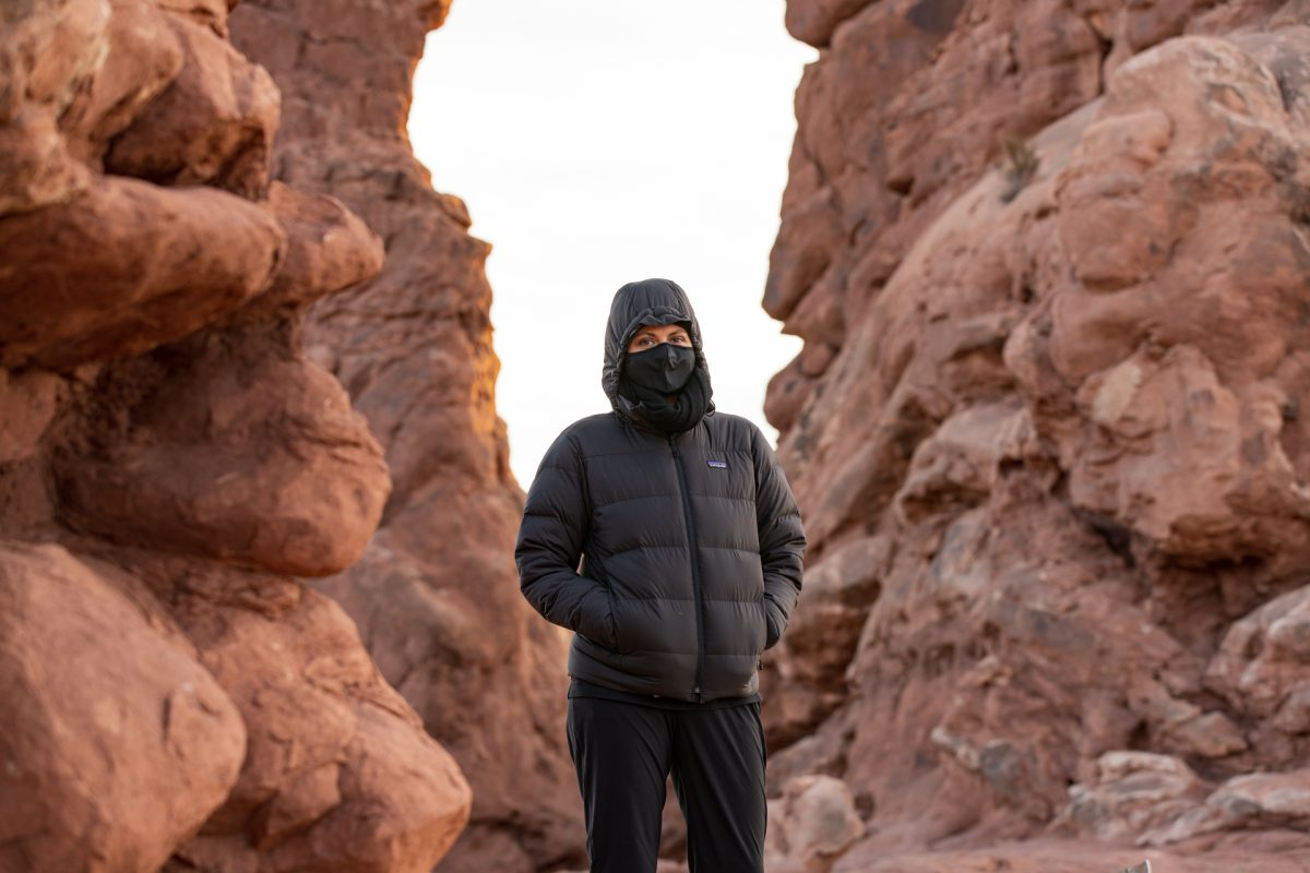 A woman wears a mask while hiking under the Turret Arch in Arches National Park in Moab, Utah.