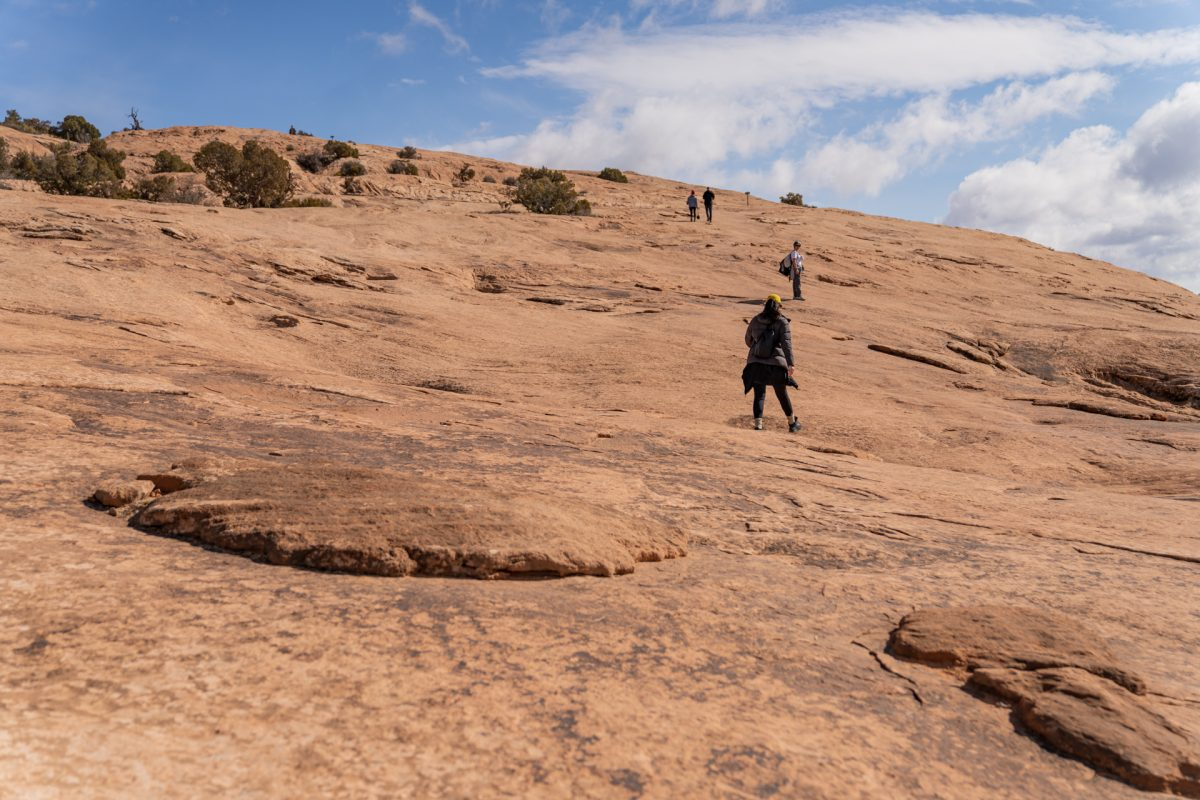 Hikers go up the steep slickrock incline on the Delicate Arch trail in Arches National Park in Moab, Utah.