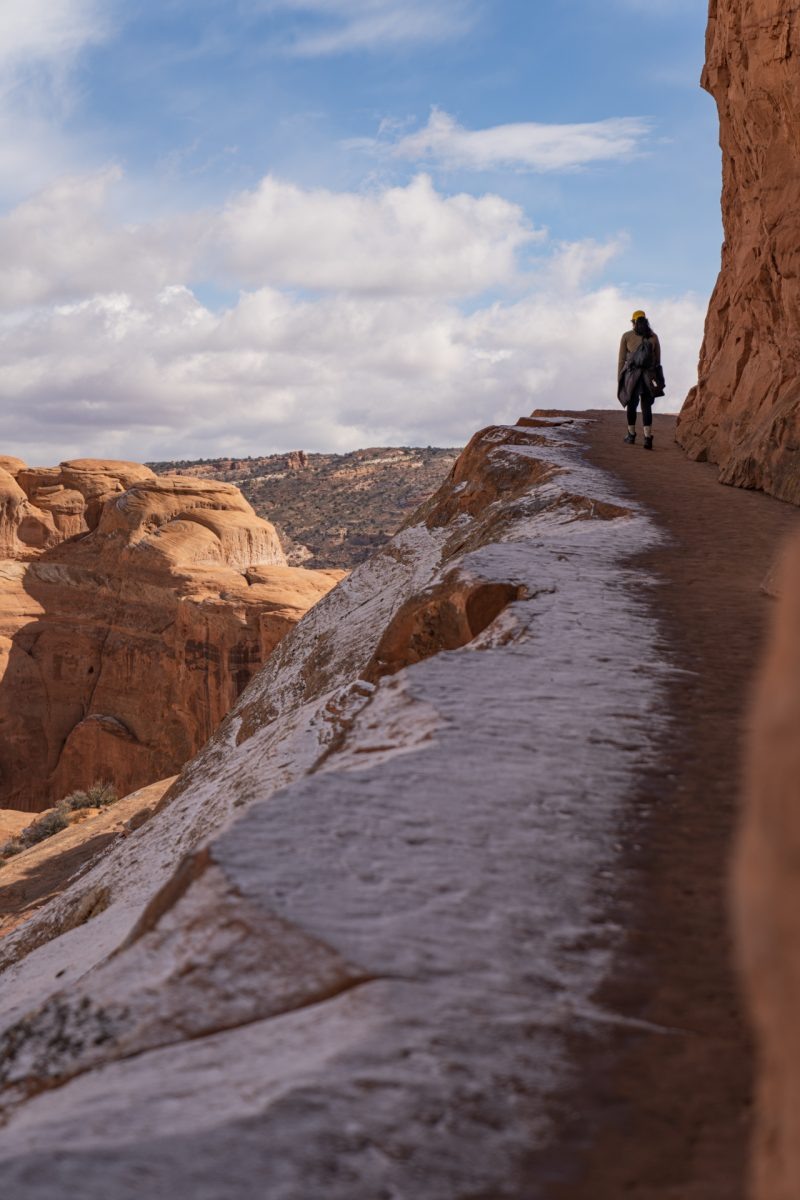 A hiker walks along the rock edge toward the end of the Delicate Arch trail in Arches National Park, Utah. Snow covers the edges of the trail.