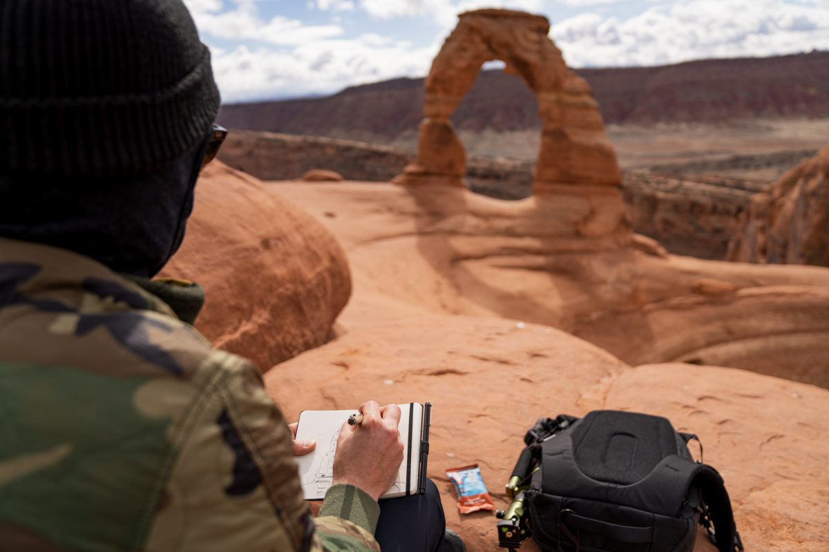 A man draws Delicate Arch with Delicate Arch seen in the background at Arches National Park in Moab, Utah.