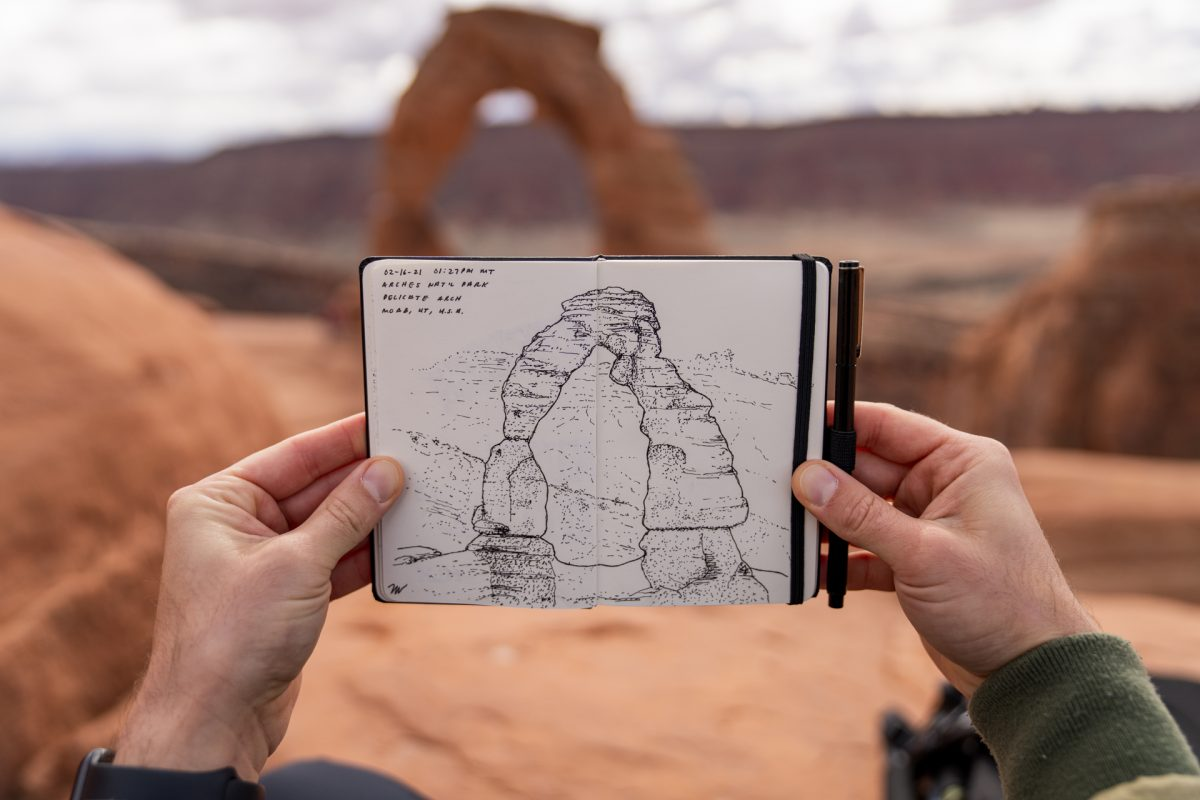 A man holds up his finished drawing of Delicate Arch with the arch in the background at Arches National Park in Moab, Utah.