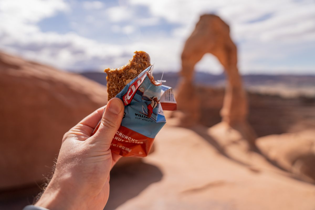 A man holds up a Clif bar while looking out to Delicate Arch in Arches National Park in Moab, Utah.